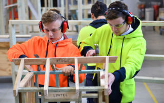 Southern Cross Catholic College Burwood students using hammers on a wooden structure